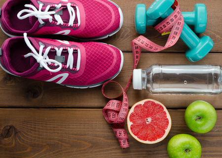 Fitness concept with sneakers dumbbells bottle of water apple pomelo and measure tape on wooden table background