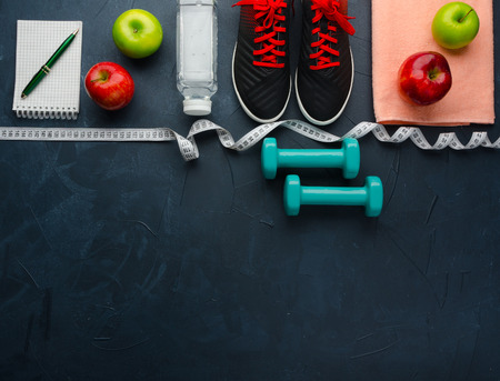 Fitness concept with sneakers dumbbells bottle of water apple and measure tape on black concrete background