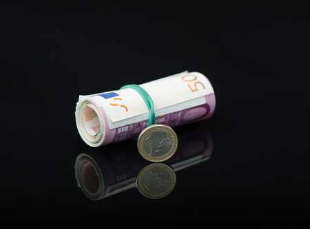 European paper money in roll and coin on black background. Business and financial concept with euro banknotes. Selective focus.
