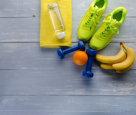 Fitness concept with sneakers dumbbells towel bottle of water bananas and oranges on blue wooden table background.