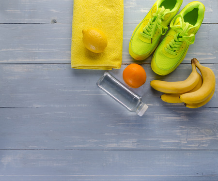 Fitness concept with sneakers towel bottle of water bananas oranges and lemons on blue wooden table background. Фото со стока