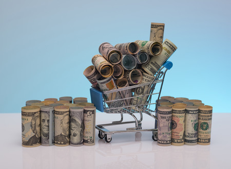 US dollars rolls and shopping cart full packs of bills on colored background with reflection. Creative business and financial concept with usa dollar banknotes