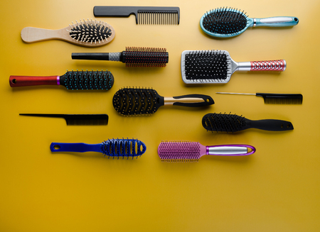 Various colored brushs and combs for hair on yellow background. Set of brush and hairbrush Фото со стока