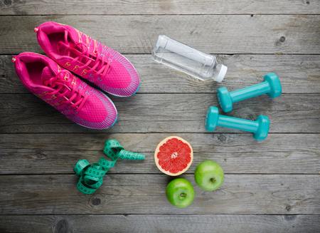 Fitness concept with sneakers dumbbells pomelo bottle of water apple and measure tape on old wooden table background Фото со стока