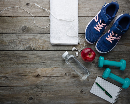Fitness concept with sneakers dumbbells bottle of water apple and headphones on old wooden table
