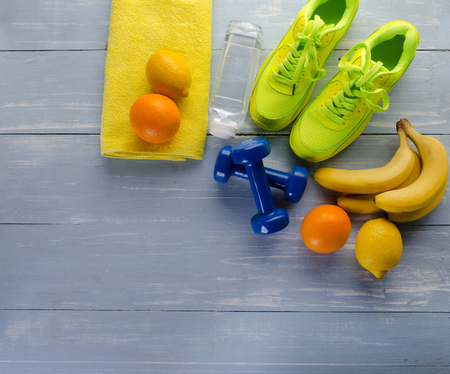 Fitness concept with sneakers dumbbells towel bottle of water bananas lemon and oranges on blue wooden table background. Фото со стока