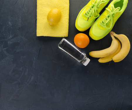 Fitness concept with sneakers towel bananas oranges and lemons on dark concrete background