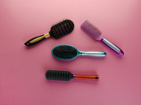 Various colored brushs and combs for hair on pink background. Set of brush and hairbrush Фото со стока
