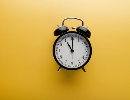 Alarm clock on yellow background top view. Concept of time