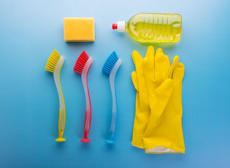 Set for cleaning. Rubber gloves, colored brushes sponge and detergent on blue background. Top view.