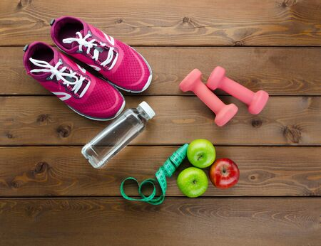 Fitness Concept with Fruits, Dumbbells, Measuring Tape, Bottle of Water and Sport Shoes on Wooden Textured Background Top Angle View. Home Training Workout, Diet, Weight Loss and Healthy Lifestyle