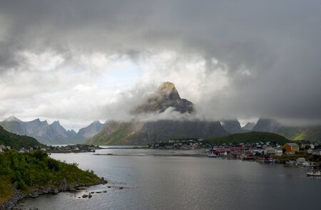 Reine, Lofoten Islands, Norway. Cloudy Aerial Landscape with Mountains, Islands, Traditional North Village and Ocean. Arctic Summer View from Above. Travel Scandinavia Concept Stock Photo