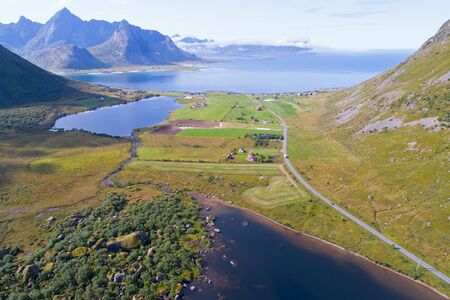 Picturesque Norway Landscape, Aerial View of Lofoten Islands with Fishing Village and Ocean. Sunny Seascape with Green Islands and Mountains on North of Scandinavia. Active Travel Concept