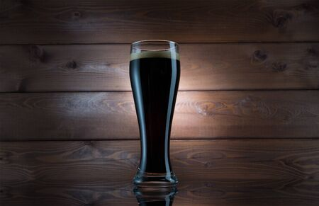 Dark Beer in Glass over Wooden Background. Isolated Mug Full of Fresh Beer without Foam on Wood Texture Closeup. Black Refreshing Alcohol Beverage, Pint of Lager or Ale Vintage Background Stock Photo