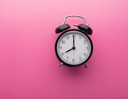 Black Retro Alarm Clock on Pink Background with Copy Space Isolated Pointing Eight O Clock. Black Vintage Countdown Clock, Morning Wake Up and Time Concept Banco de Imagens