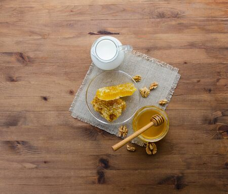 Breakfast composition with fresh honey, dipper, honeycomb, milk and nuts on textured wooden background. Tasty delicious and nutritious rural morning set. Harvest and beekeeping concept Stock Photo