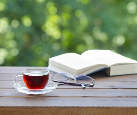Cup of hot tea, eyeglasses and open book on old wooden table over beautiful green foliage bokeh background. Summer or spring morning relaxation and refreshment outdoors with view of garden or forest