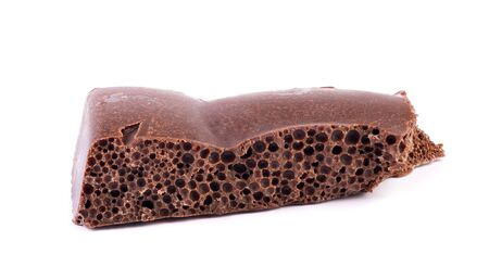 Porous chocolate bar isolated on while background. Detailed chocolate with air bubbles closeup. Milk or dark chocolate. Cocoa dessert yummy and delicious Stock Photo