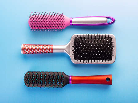 Comb brushes set. Several hairbrushes for female hair on blue background. Combs of different size and form isolated. Hairdressing and hairstyle concept