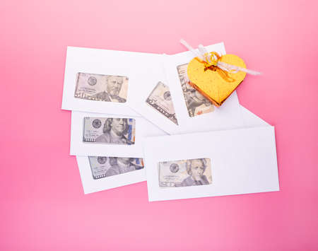 Envelopes with dollar bills and golden gift box on pink background, top view with copy space. Business bonus, donation, corruption and bribes concept