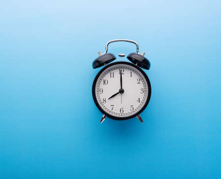 Black retro alarm clock showing eight o'clock, closeup top view clipping path, isolated on blue background. Time, deadline and morning routines concept 版權商用圖片
