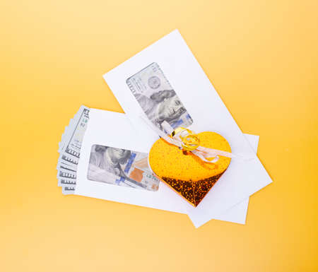 Golden gift box over envelopes full on dollar banknotes, top view. Illegal donation, economics, earnings, business bonuses and corruption concept