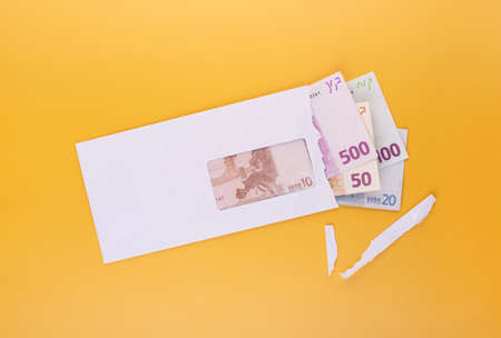 Open envelope with euro banknotes on yellow background, top view. Money for salary, bonus for successful work, compensation or corruption bribery concept 版權商用圖片