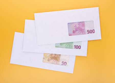 Stack of closed white envelopes with euro bills inside over yellow background. Concept of income, bonuses or bribes. Corruption in business, illegal black salary 版權商用圖片