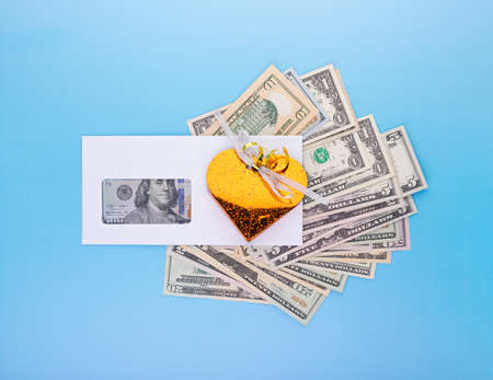 Financial business success, bonuses in salary and high revenue and profit rate concept with gift box over dollar bills pile on blue background, top angle view 版權商用圖片