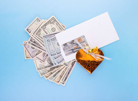 Gift box over pile of envelopes with dollar banknotes, top angle view. Business bribery, salary bonuses for successful work or corruption concept
