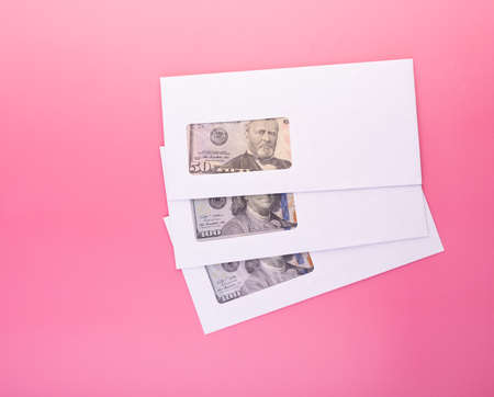 Stack on white envelopes with dollar bills inside over pink background with copy space. Concept of income, bonuses or bribes. Corruption, salary template 版權商用圖片