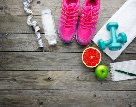 Fitness, lose weight and home training concept with sport equipment, shoes, fruits and measuring tape on old wooden background with copy space, top view