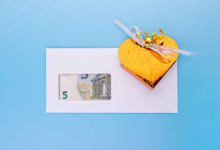 Money and gift box for holiday event present, retirement bonus or success at work revenue. Business financial income concept. Top angle view on blue background