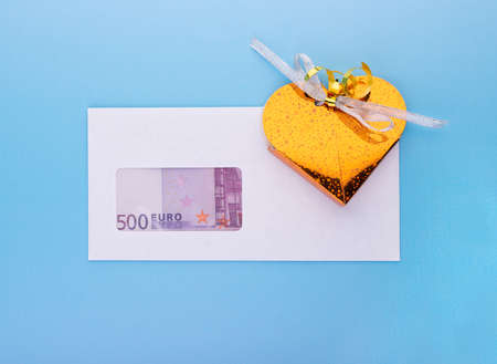 Business investment dividends or salary bonus for holiday event concept with gift box over while blank envelope with euro banknotes, top angle view