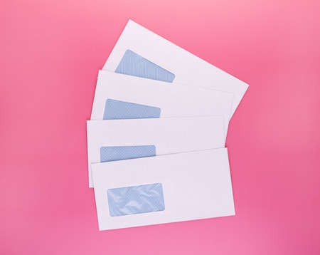 Blank envelopes with address window isolated on pink background. White paper envelopes mockup for business correspondence, postal stationery and corporate lettering 版權商用圖片