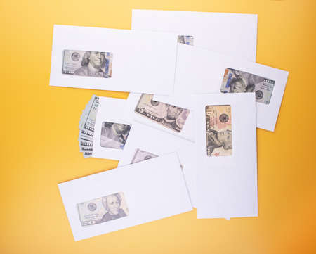 Pile of envelopes with dollar banknotes, top angle view. Business bribery, salary bonuses, corruption or savings concept. Home and business finances