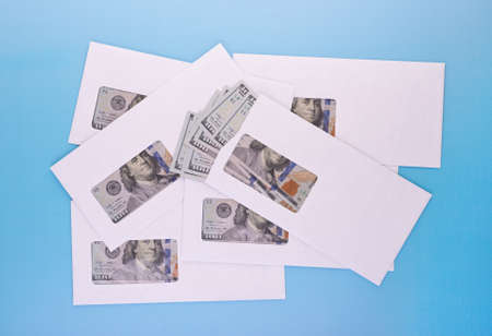 Dollar bills in closed white envelopes for business bonuses, illegal salary, revenue, corruption, bribery or donation concept. Top angle view 版權商用圖片