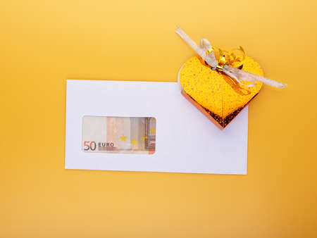 Money for present concept with euro banknotes in envelope and gift box isolated on yellow background, top angle view. Business bonus or salary increase