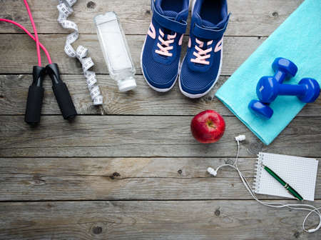 Fitness equipment, Dumbbell, shoes, water bottle and fruits on wooden floor, top view with copy space. Health, nutrition, home training and sport concept 版權商用圖片