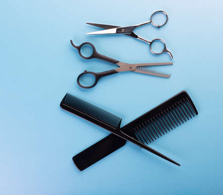 Professional tools for hairdresser isolated on blue background: hair combs and haircutting scissors. Hairdresser equipment for hairstyle in salon or barbershop concept