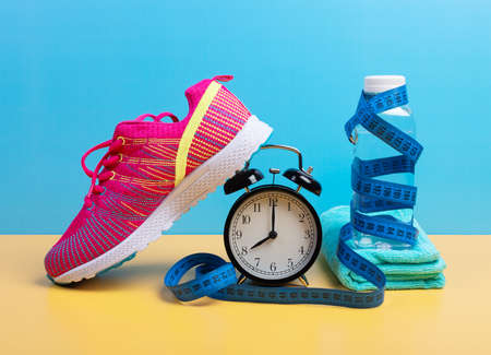 Weight loss and training concept with measuring tape, bottle of water, towel and sneaker over blue wall background. Fitness and running equipment set