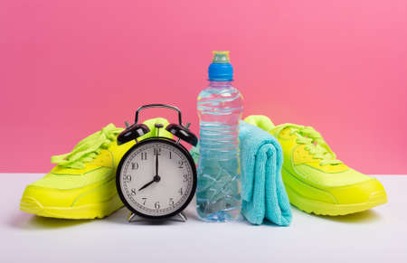 Training and healthy lifestyle concept with equipment for jogging or fitness: sport shoes, bottle of water, towel and clock over pink wall background 版權商用圖片
