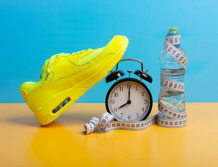 Fitness, wellbeing and home or gym exercises concept with shoes, water bottle and measure tape over blue wall background. Sport training, running and weight loss