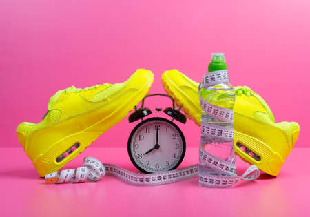 Set of sport shoes, alarm clock, bottle of water and measuring tape over pink background. Training, gym exercising, running and jogging concept 版權商用圖片
