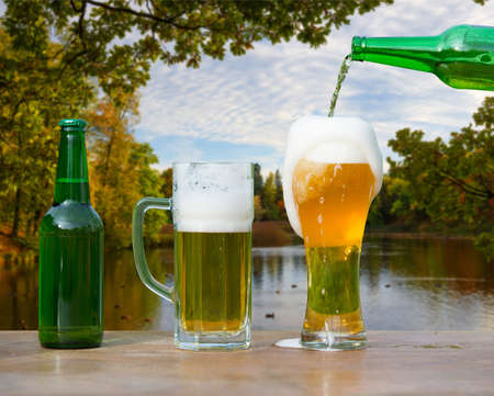 Pouring glass of beer from bottle on autumn yellow park and lake background 版權商用圖片