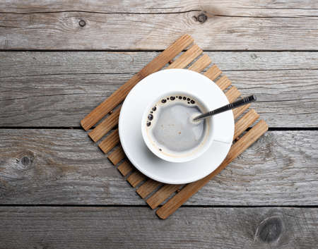 A cup of hot coffee on old wooden table in a cafe. White cup of coffee in the morning. 版權商用圖片