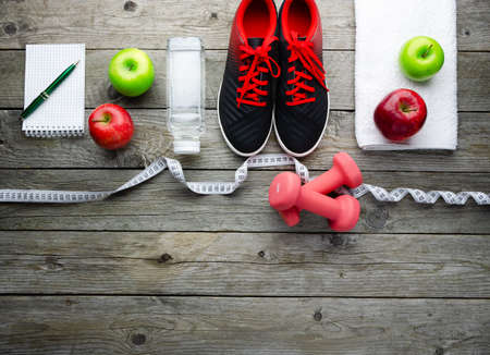 Fitness equipment with shoes, fruits, and measuring tape on old wooden 版權商用圖片