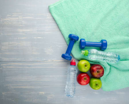 Healthy lifestyle concept. Colored Apples dumbbells sport water bottles and turquoise towel on blue wooden table background. 版權商用圖片