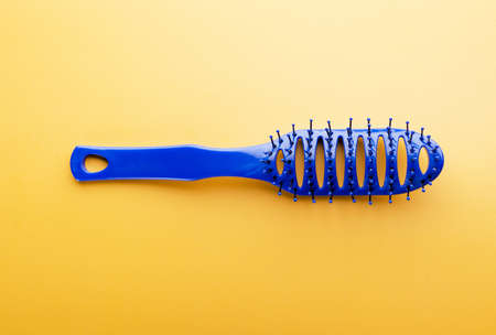 Hairstyle concept with hair brush on yellow background. Fashion, beauty and hygiene. Plastic comb for salon and home usage