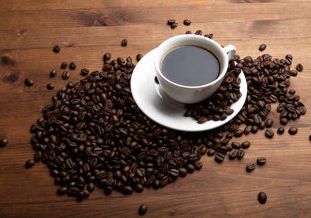 Coffee beans and cup of coffee on old wooden table. Coffee in a white cup. 版權商用圖片